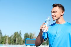 Young sporty man drinking water from bottle at stadium on sunny day stock image