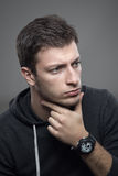 Young sporty man with hand under chin thinking and looking away Royalty Free Stock Photo