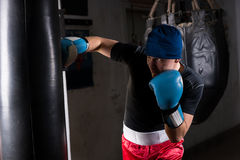 Young sporty man in a hat and boxing gloves training with boxing Royalty Free Stock Images