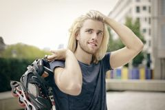 Sporty young man with skates Royalty Free Stock Photo