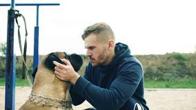 Free Young Sporty Man Hug And Play His Bullmastiff Dog Outdoor At Nature Stock Images - 105771504