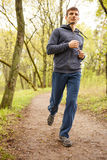 Young sporty man jogging in the morning forest Royalty Free Stock Images