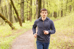 Young sporty man jogging in the morning forest Stock Photo