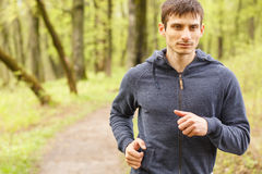 Young sporty man jogging in the morning forest Stock Photography