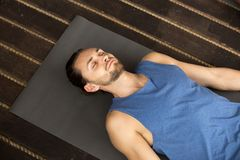 Young sporty man lying in Dead Body exercise. Or Corpse pose with his eyes closed, Savasana pose, working out, resting after practice, indoor close up, studio Stock Photography
