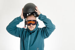 Man with goggles putting on ski helmet Stock Photo