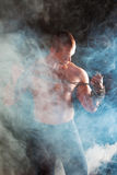 Young sporty man over Smoke. Royalty Free Stock Photos