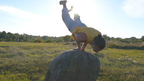 Young sporty man practicing difficult advanced yoga pose at nature. Caucasian guy doing yoga moves and positions Stock Photography