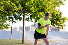 Young sporty man read text message on his smart phone while taking break during morning jog in beautiful urban park Royalty Free Stock Photography