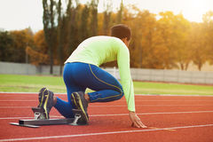 Young sporty man are ready to run on racetrack. Fit well formed people at large nice modern stadium Royalty Free Stock Images