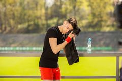 Young sporty man resting and wiping his sweat with a towel after workout sport exercises outdoors. On the background of green grass royalty free stock images