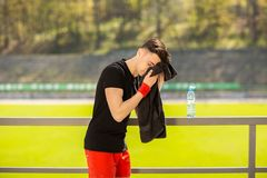 Young sporty man resting and wiping his sweat with a towel after workout sport exercises outdoors. On the background of green grass stock image