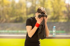 Young sporty man resting and wiping his sweat with a towel after workout sport exercises outdoors stock photo