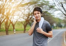 Young sporty man resting and wiping his sweat with a towel after. Workout sport exercises outdoors at the park royalty free stock photo