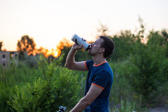 Young sporty man riding a bicycle drinking water from the sport bottle at sunset Stock Images