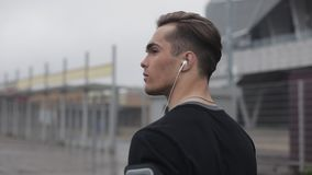 Young sporty man runner with earphones, walking near stadium. Back side view.