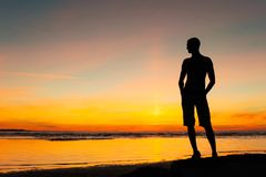 Young sporty man silhouette standing on the beach at sunset. Young sporty man silhouette standing on the beach at multicolored sunset. Summertime vibrant Royalty Free Stock Photo