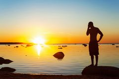 Young sporty man silhouette standing on the seashore at sunset. Young sporty man silhouette standing in doubt on the seashore at vibrant multicolored sunset Royalty Free Stock Photos