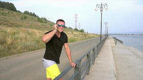 Young sporty man in sunglasses talking on the phone on the seafront stock footage