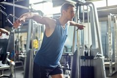 Exercising on Cable Crossover Machine. Young sporty man using cable crossover machine while having intensive workout, interior of modern gym on background stock images