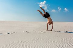 Young sporty man want doing acrobatic exercises on the sand near river. Portrait of young parkour man Royalty Free Stock Image