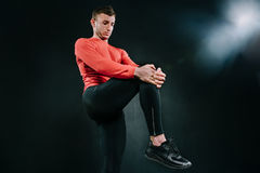 Young sporty man wearing red sportswear and stretching his leg after a heavy workout in dark background. Powerful handsome athleti. Caucasian sportsman wearing Stock Photography