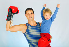 A young sporty men with son. A young sporty men in a red boxing gloves with son royalty free stock photos