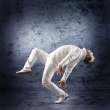 A young male dancer performing in white clothes Stock Images
