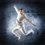 A young male dancer performing in white clothes. Young and sporty modern dancer over the dramatic background Stock Photos