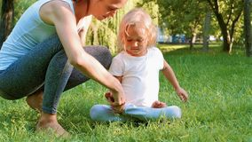 Young sporty mother coaching her little cute daughter doing yoga exercise. In a green park. Mom helps her daughter to sit down in the lotus position stock image