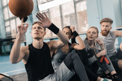 Young sporty people looking at man balancing ball on finger Royalty Free Stock Photography