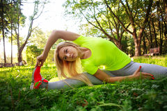 Young sporty woman doing fitness exercises stretching in park. Young sporty slim woman doing fitness exercises stretching in green city park Stock Photos