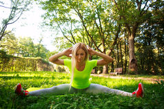 Young sporty woman doing fitness exercises stretching in park. Young sporty slim woman doing fitness exercises stretching in green city park Royalty Free Stock Photo