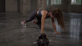 Young sporty stylish woman train her body workout her muscles indoor at empty studio. Athletic beautiful styylish woman