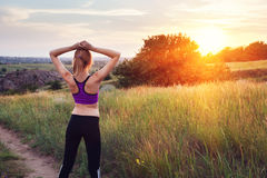 Young sporty woman with arms raised up at sunset Stock Photography