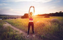 Young sporty woman with arms raised up at sunset Royalty Free Stock Image