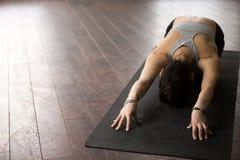 Young sporty woman in Balasana pose, white loft studio, copyspac Royalty Free Stock Image
