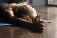 Young sporty woman doing breathing exercise lying on the floor. Young sporty attractive woman practicing yoga, doing breathing exercise, relaxation pose, working stock image