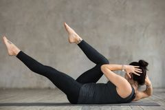 Young sporty woman doing crisscross exercise. Young slim woman practicing fitness, doing crisscross exercise, bicycle crunches pose, working out, wearing royalty free stock photos