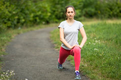 Young sporty woman doing exercise warm-up before running in park in summer day. Stock Image