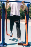 Young sporty woman doing exercises for legs on the playground in Royalty Free Stock Images