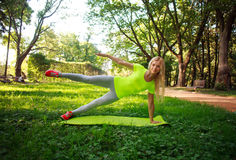 Young sporty woman doing fitness exercises stretching in park. Young sporty slim woman doing fitness exercises stretching in green city park Stock Photography
