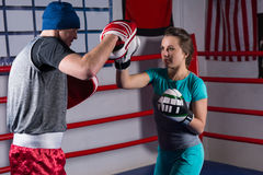 Young sporty woman doing kickboxing training with her coach stock images