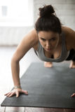 Young sporty woman doing press ups exercise, white loft studio Royalty Free Stock Image