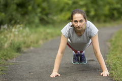 Young sporty woman doing push-ups in park in summer day. Royalty Free Stock Photos