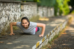 Young sporty woman doing push-ups in park in sunshine on beautiful summer day. Royalty Free Stock Photography