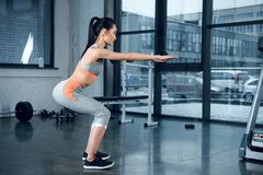 young sporty woman doing squats with outstretched hands stock photos