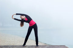 Young sporty woman doing stretching exercises during fitness tra Royalty Free Stock Photography