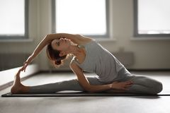 Young sporty woman doing yoga stretching exercise sitting in gym near bright windows Stock Images