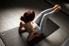 Young sporty woman doing yoga stretching exercise sitting in gym near bright windows Royalty Free Stock Photo